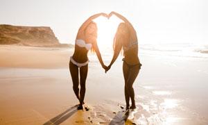 沙滩上比划出心形的比基尼美女图片