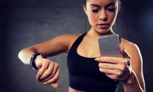 在查看运动数据的健身美女高清图片