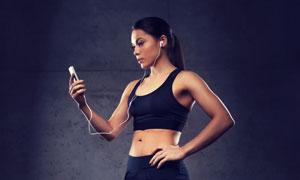 叉腰看手机的健身美女摄影高清图片