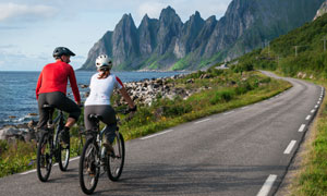 濒临大海山峰公路上的骑行人物图片