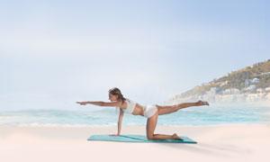 海边沙滩上练习瑜伽的美女高清图片