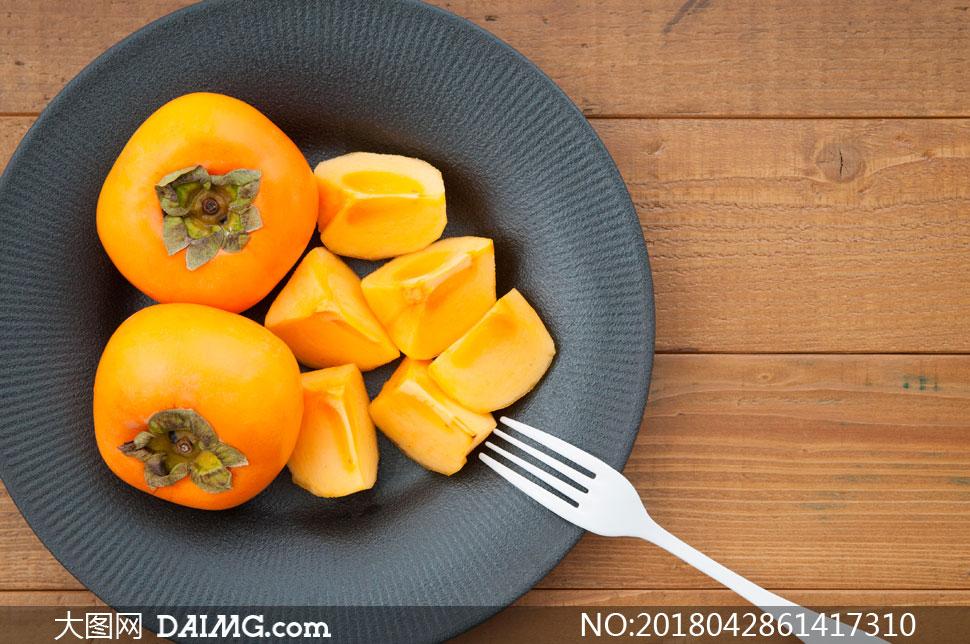 盘在中切开的柿子特写摄影高清图片