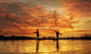 往湖里撒下渔网的人物剪影高清图片