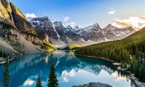 树林湖泊与高低起伏的雪山高清图片