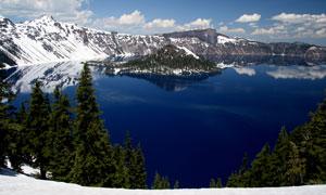云朵与环绕湖泊的雪山摄影高清图片