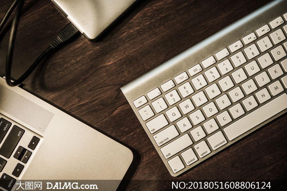 桌上的笔记本电脑与键盘等高清图片