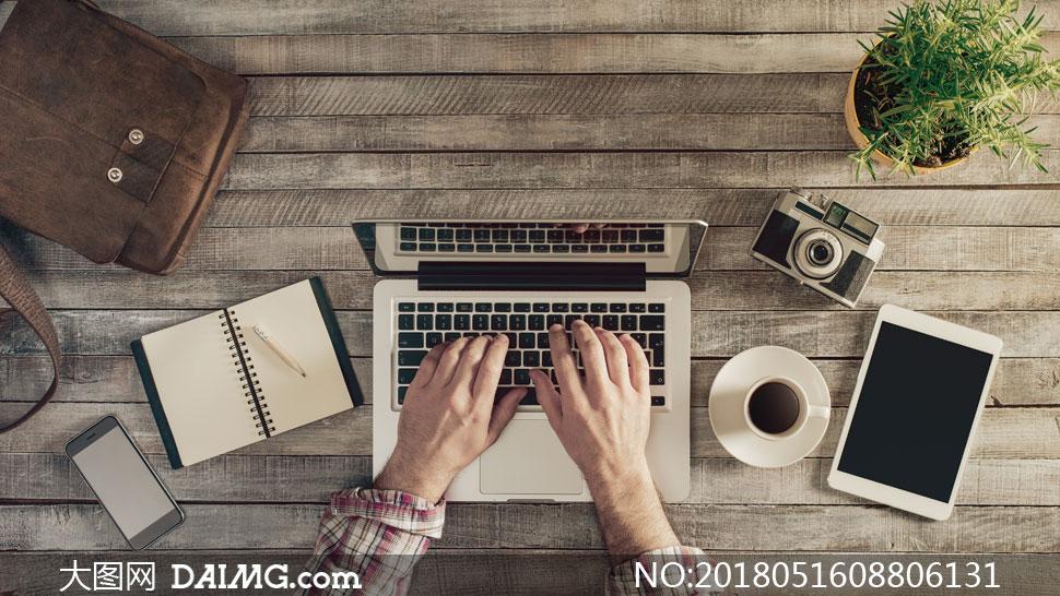 记事本与在操作电脑的双手高清图片