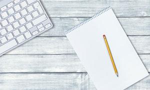 桌面上的键盘与记事本摄影高清图片