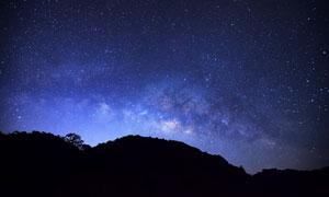 星空與遠處的山巒剪影主題高清圖片
