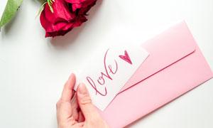 红玫瑰花与手里的信封摄影高清图片
