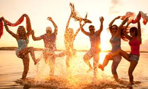 在海邊載歌載舞的開心男女高清圖片