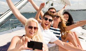 游艇上对着手机自拍的男女高清图片