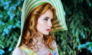 头戴遮阳帽的卷发美女摄影高清图片