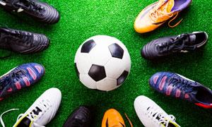 放摆在足球四周的几只球鞋高清图片