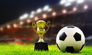 体育场草地上的足球与奖杯高清图片