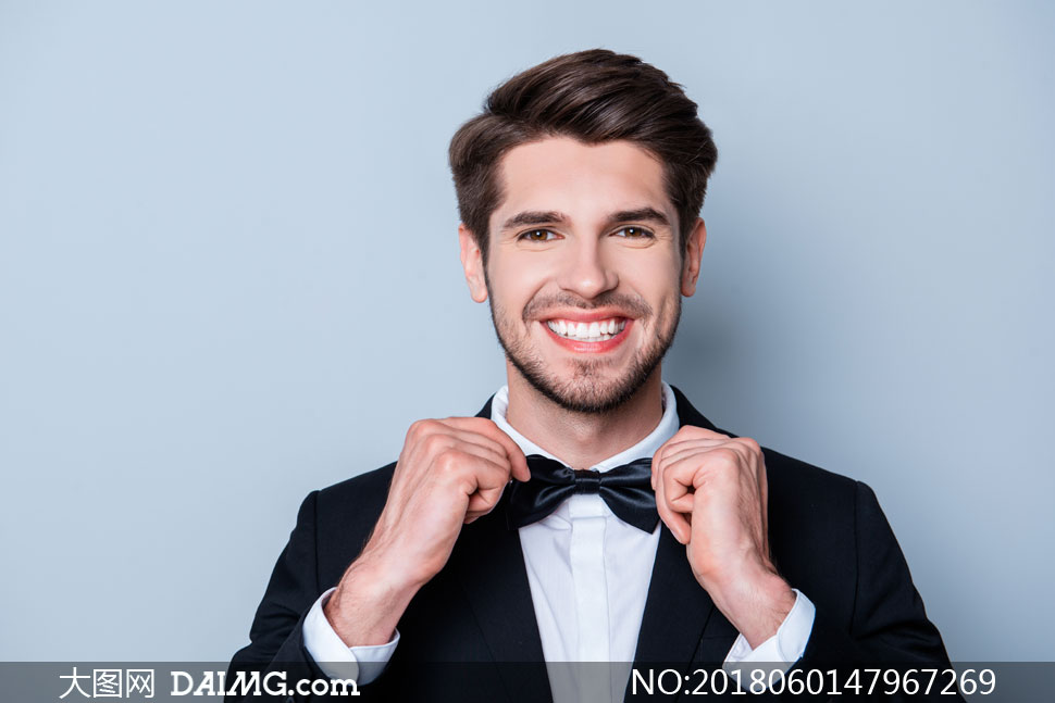 双手在整理领结的开心帅哥高清图片