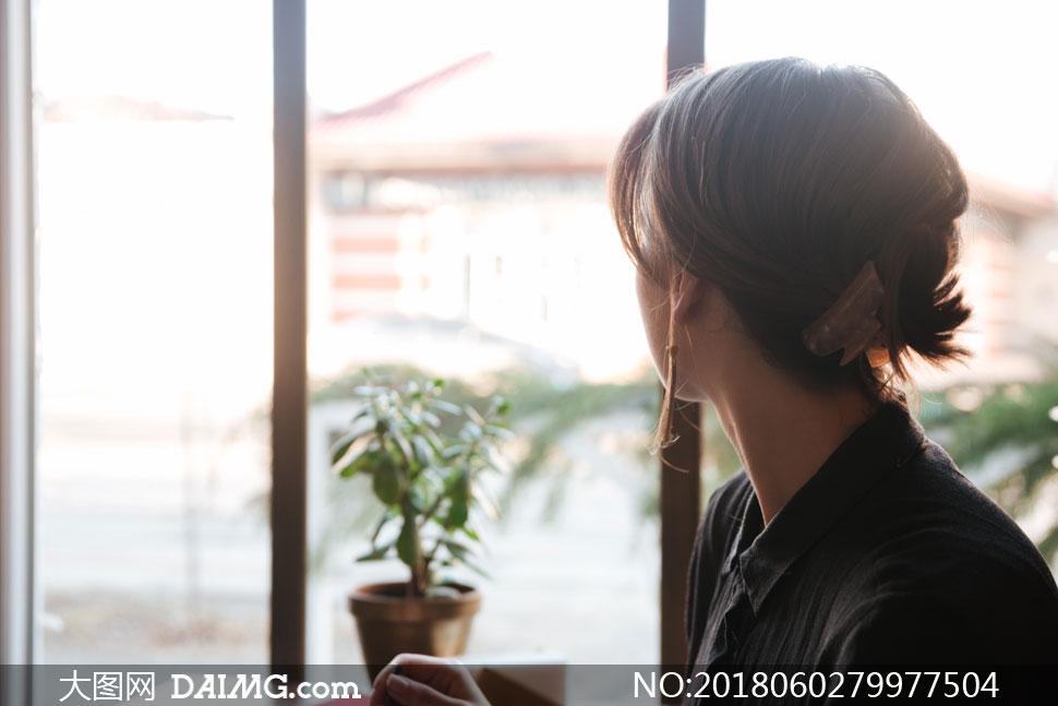 扭头看窗外风景的美女摄影高清图片