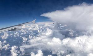 云端上的飞机机翼一角摄影高清图片