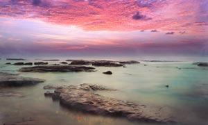 海边黄昏下的礁石美景摄影图片