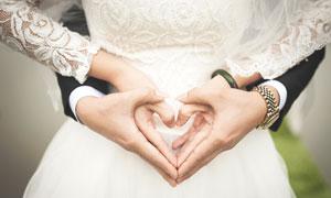 新娘新郎比划出的心形特写高清图片