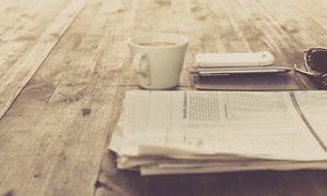 桌上的咖啡杯与报纸等物品高清图片