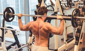在举着杠铃的肌肉男子摄影高清图片