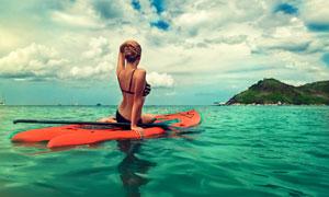 天空大海与在皮艇上的美女高清图片