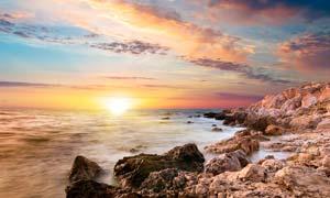 海边礁石和夕阳美景摄影图片