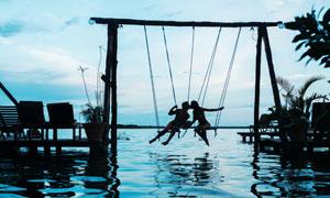 在水面上荡秋千的情侣摄影高清图片