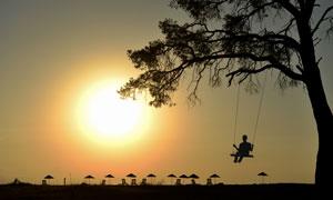 夕阳下在荡秋千的人物剪影高清图片