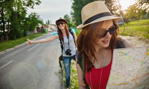 路边看地图等车的美女摄影高清图片