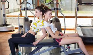 背靠背坐着休息的运动美女高清图片