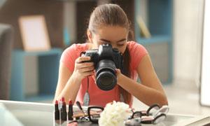 在拍摄口红等化妆品的美女高清图片