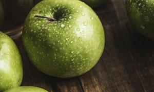 表面挂着水珠的青苹果摄影高清图片