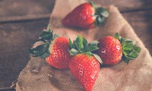 在麻袋片上的几个草莓摄影高清图片