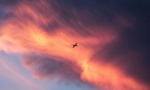 瑰丽云彩中的民用飞机摄影高清图片
