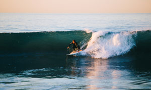 辽阔大海上冲浪的男人摄影高清图片