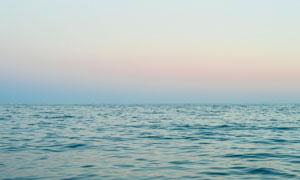 天边霞光与平静的海面摄影高清图片