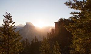 大山与山间的树林逆光摄影高清图片