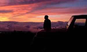 坐车头上看日落的人物剪影高清图片