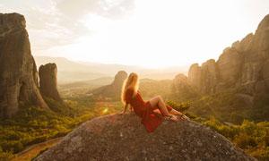山中石头上的红裙美女摄影高清图片