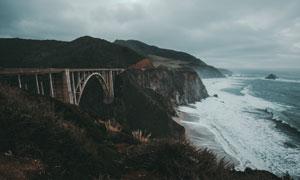 山丘桥梁与海边的波浪摄影高清图片