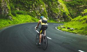 山间公路上骑行的男子摄影高清图片