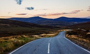 柏油公路与远处的山峦摄影高清图片