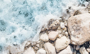 拍打着海边沙子石头的海水高清图片