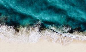 沙滩浪花与海上的小船摄影高清图片