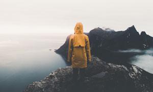 站在海边礁石上的风衣人物高清图片