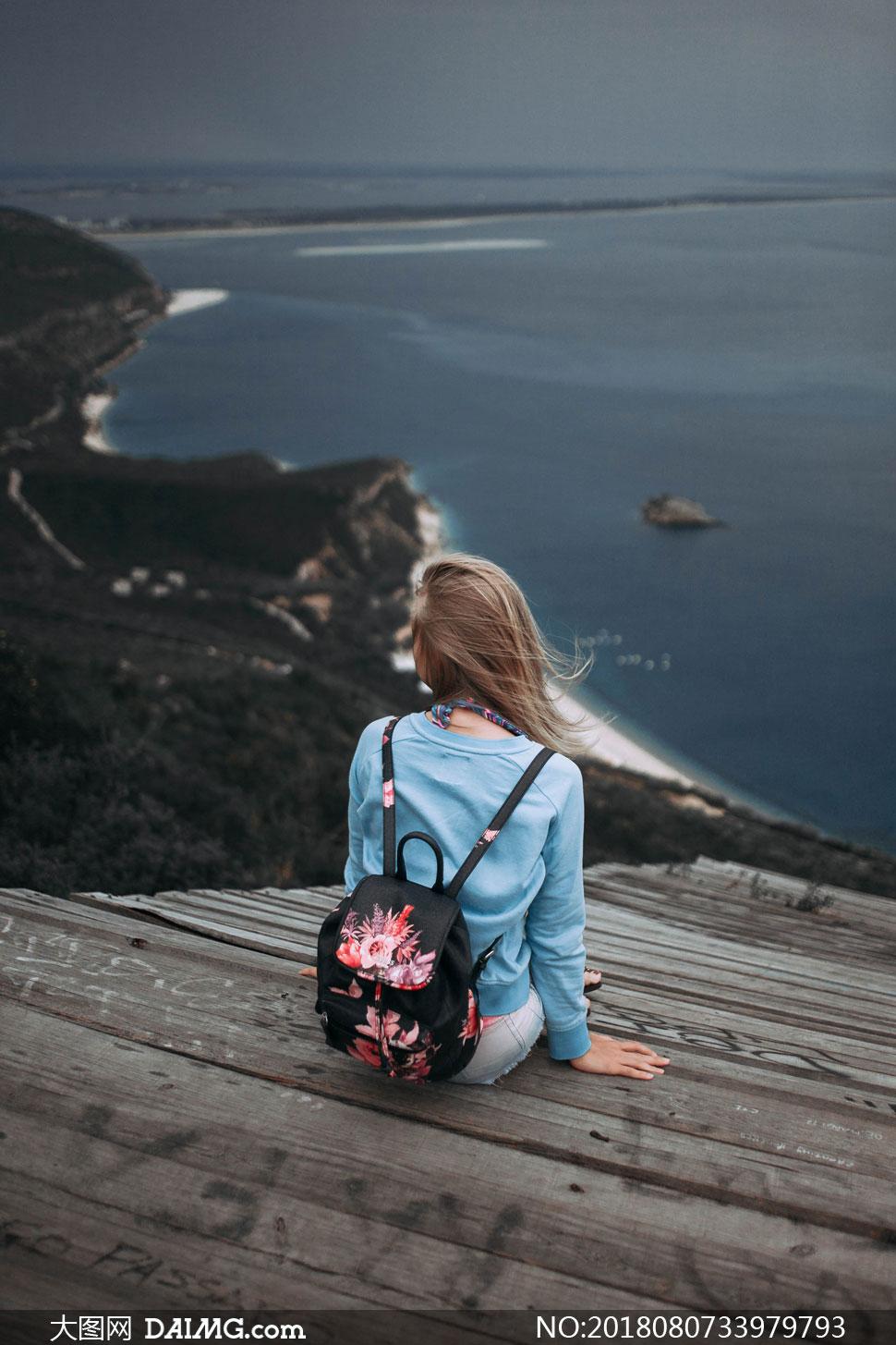 坐在海边台阶上的美女人物高清图片
