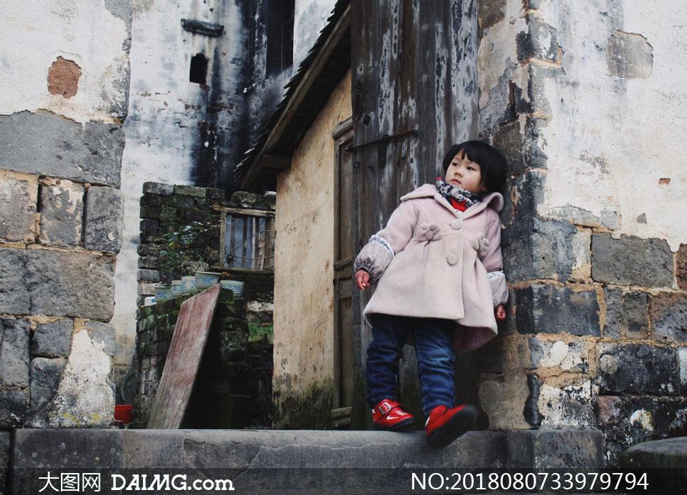 靠在门边的冬装小女孩摄影高清图片