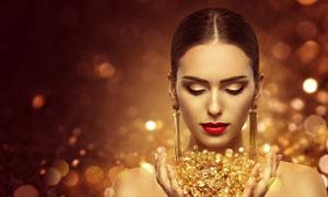 手捧着金色饰品的红唇美女高清图片